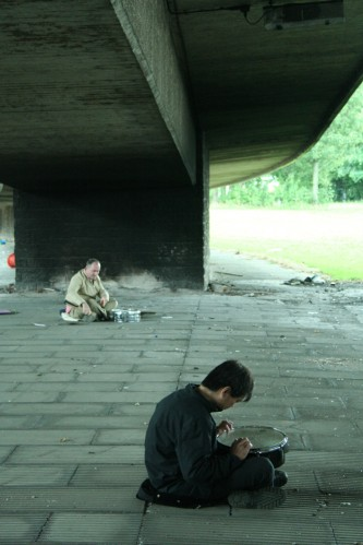 Two men with snare drums playing under a dirty motorway