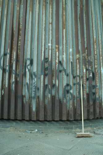 A corrugated iron wall with a brush against it