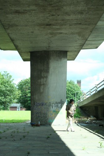 Tamio playing saxophone beneath a concrete motorway structure
