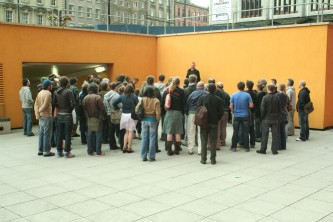 Audience assembled around a speaker near an orange wall in Newcastle