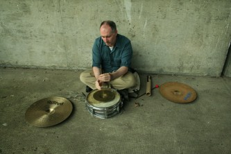 Sean meehan playing percussion on the ground in a concrete corner