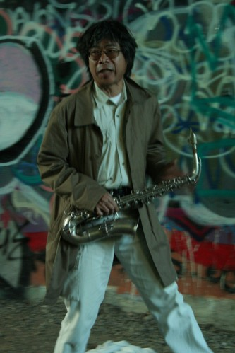 Tamio Shiraishi with saxophone against graffiti covered walls, white jeans