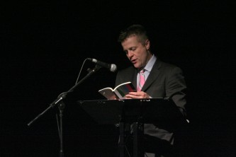 Christian Bok reads behind a lectern in a pink tie and suit