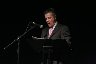 Christian Bok reads behind a lectern in a pink tie and grey suit