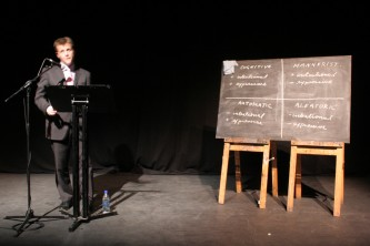 Christian Bok reads behind a lectern in a pink tie beside a blackboard