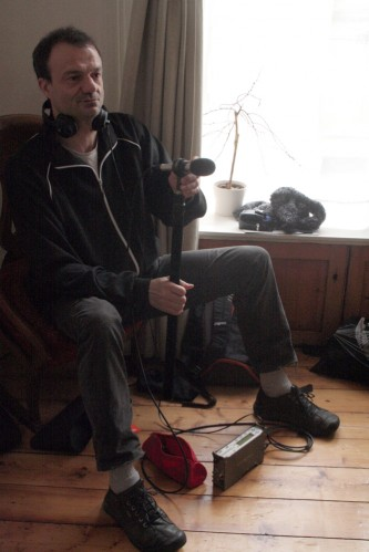 Jean-Luc Guionnet sitting in a home with a microphone and recording gear