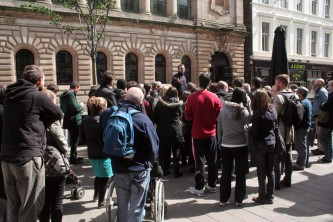 A group of people huddle round a speaker in George Square, Glasgow
