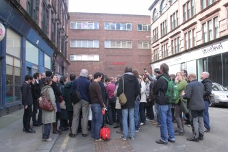 People standing in a huddle on a street in Glasgow's Merchant City