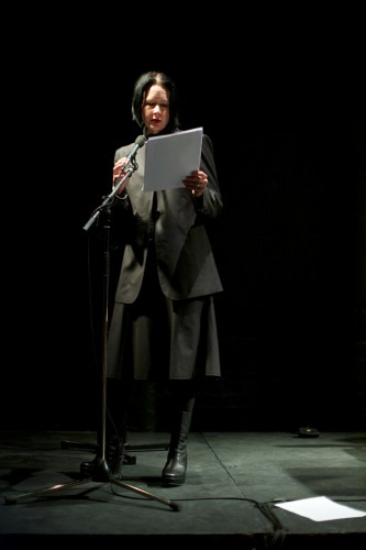 Vanessa Place reads from white papers in a black room