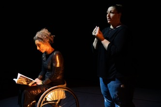 Alice sits, reading from a book, behind her the ASL interpreter gestures