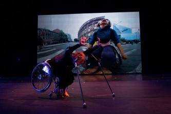 Alice leans forward whilst seated in her chair, with a film projected behind
