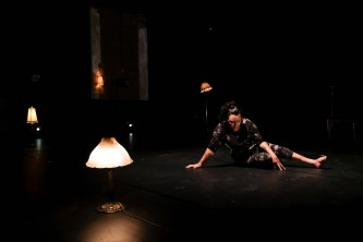 NEVE sits on the floor, arms reaching forwards, the floor covered in lit lamps
