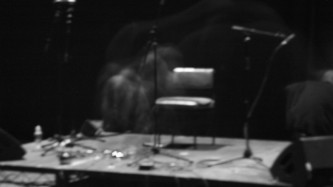 A spectral Keiji Haino hardly visible on stage in near darkness