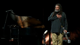 Wadada Leo Smith thanks the audience, hand on his heart, trumpet by his sideide