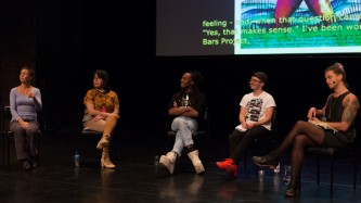 Four people on stage have a discussion. A screen projects images behind them