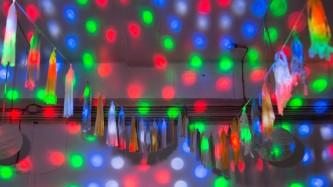 blue red and green circles of light falling on a wall among decorations