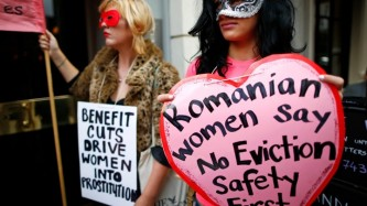 Women stand with protest signs wearing masks