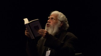 Samuel R. Delany white hair and beard reading on stage at EPISODE 9