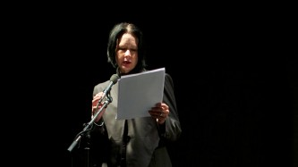 Vanessa Place reading from white papers in a black room