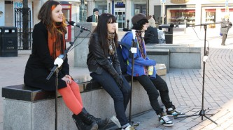 Three people sit in Dundee city centre speaking into microphones