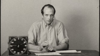 A man sits at a desk with a large timer clock on it and speaks to camera