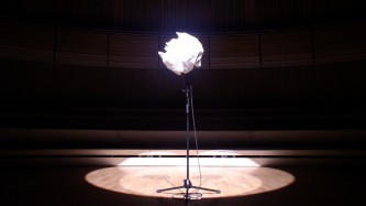 A microphone wrapped in white paper on a mic stand on stage