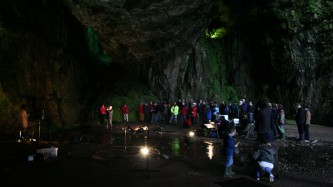 An audience assembled inside a cave a pool of water between them and performers