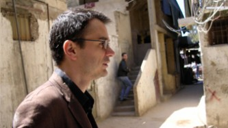 Ray Brassier walks along a sunny street in Beirut, he is in profile