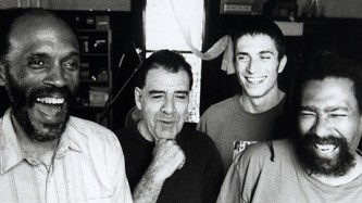 A B&W portrait of four members of TEST, all smiling