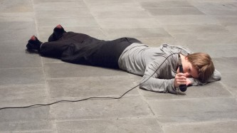 a participant lies on the gallery floor face down and hits the floor with a mic