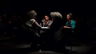 Four people sat around a table on a stage. They are having a discussion.