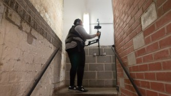 Sondra Perry in a stairwell wearing a Steadicam harness