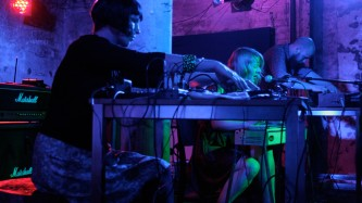 Three performers on stage, two on electronics and one sings