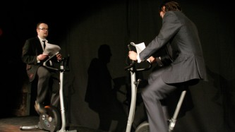 Two men in suits and ties ride exercise bikes whilst reading from books