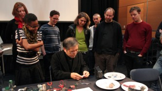 A group gather as Tetsuo Kogawa shows folks how to make a radio