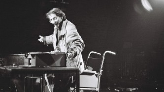 Henri Chopin on stage smiling and operating a tape recorder