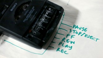 A tape recorder on a piece of paper that reads play, stop, pause and record