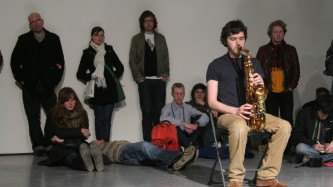 Marc Baron plays saxophone on a chair, audience around