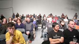 A brightly lit audience display a mixture of emotions