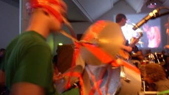 a man in green clothes is wrapped to a drum kit by red tape