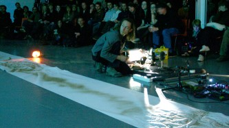 A man crouching before an audience operating a projector