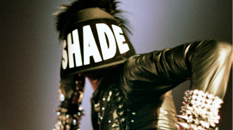 A figure in leather and studded cuffs wears a large visor with the word SHADE