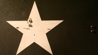 A white star painted on a black oil tank or similar metal container
