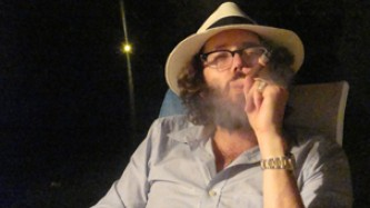 Alexi Kukuljevic in a Panama hat smoking a massive cigar