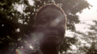 The sun coming through trees behind poet Hortense Spillers creates a lens flare