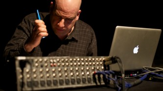 A man with a torch looking at a mixing board