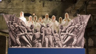 A chorus in white boiler suits stand behind a concrete frieze of Russian workers