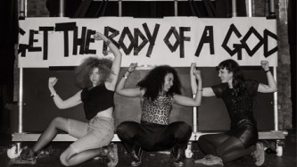 "Three women pose in front of a home made banner ""Get the Body of a God"""