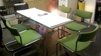 A small room with a table with white paper on it and several green chairs