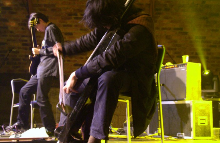 Exias J playing guitars and double bass on stage at INSTAL 04